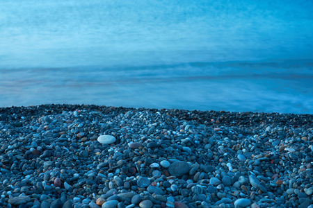 Pebble beach with blurred seawater on a background. Copy space.