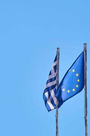 Flags of Greece and Europe against a clear blue sky. Copy space.