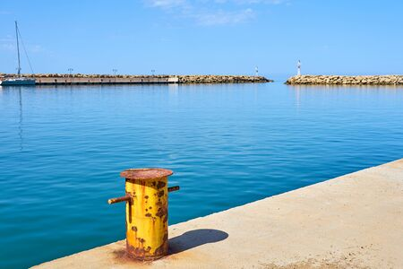 Old Rusty yellow Iron Mooring Bollard in harbor. Sea coast. Copy space.