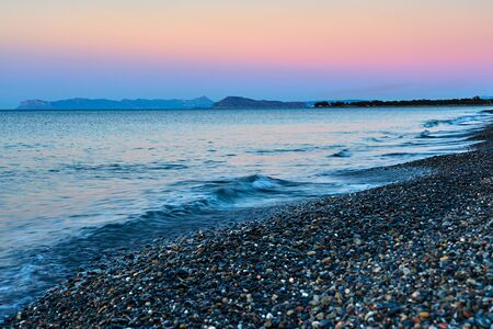 Pebble beach with waves on a sunset. Crete, Greece. Stock Photo