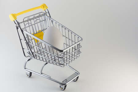 A shopping cart with an egg on a white background. Copy space.