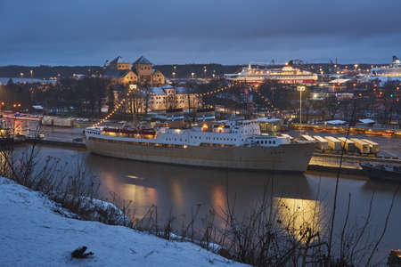 TURKU, FINLAND - January 01, 2021: View of the ship hostel Bore and Turku Castle at dusk. Copy space.