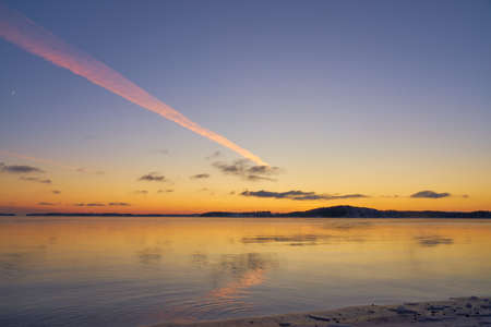A trail from the plane in the sunset sky with reflections on water. Copy space.