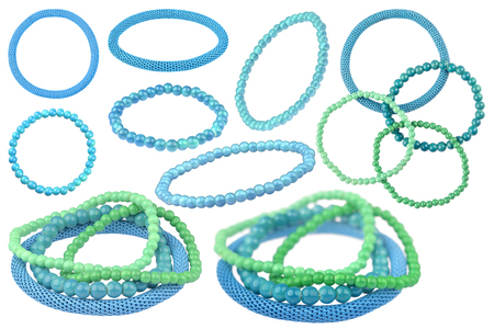 Many instances of blue and green elastic bracelets made of pearl-like round beads and one blue metallic elastic bracelet, isolated on white background, clipping paths included