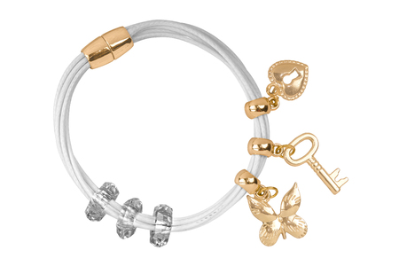 personal ornaments: White textile bracelet with golden ring and gold charms decorations, isolated on white background, clipping path included Stock Photo