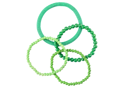 personal ornaments: Set of three green elastic bracelets made of pearl-like round beads and one green metallic elastic bracelet, isolated on white background, clipping path included