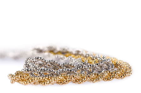Macro detail of two golden and silver metallic headbands made of multiple weaved golden and silver fibers, very shallow depth of field, fashion item isolated on white background