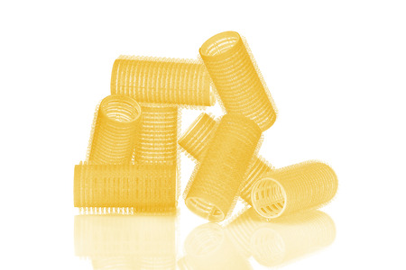 Set of eight yellow hair curlers isolated on white background, with nice reflexion.