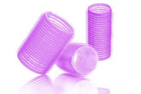 Set of three different sizes purple hair curlers, isolated on white background, with reflection