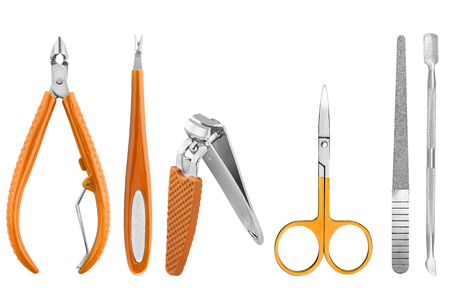 Six stainless steel nails care basic instruments, some with orange rubber cover: two-pronged dead skin scissor and cuticles pliers, two cuticle pushers, nail clippers, nail file and nail scissors, beauty products isolated on white background Stock Photo