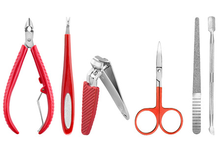 Six stainless steel nails care basic instruments, some with red rubber cover: two-pronged dead skin scissor and cuticles pliers, two cuticle pushers, nail clippers, nail file and nail scissors, beauty products isolated on white background