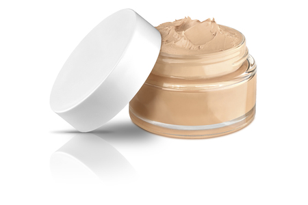Nice glass face make-up creme foundation open container with a white plastic lid and smeared creme, isolated on white background and with reflections and shadows Stock Photo