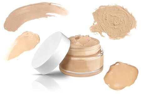 Luxury glass face make-up creme foundation open container and four smeared color samples, isolated on white background