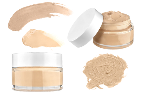 Luxury glass face make-up creme foundation open and closed container and three smeared color samples, isolated on white background