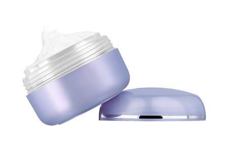 Facial cosmetic creme in blank purple blue glossy open jar sitting on it`s lid on one side, beauty product isolated on white background