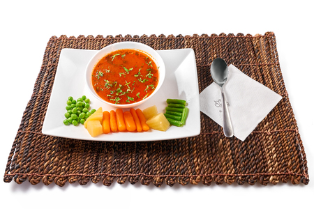 Traditional Romanian vegetables soup chorba with tomatoes sauce (Ciorba de legume). On white plate with fresh vegetables, and on brown wattle place mat, isolated on white background