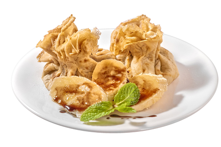 Traditional Romanian crepes with banana slices, hazelnut spread with cocoa and mint leaves decoration, on white plate and isolated on white background
