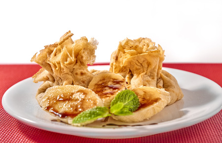 Traditional Romanian crepes with banana slices, hazelnut spread with cocoa and mint leaves decoration, on white plate and red place mat, isolated on white background