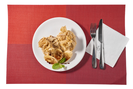 minted: Traditional Romanian crepes with banana slices, hazelnut spread with cocoa and mint leaves decoration, on white plate and red place mat, isolated on white background
