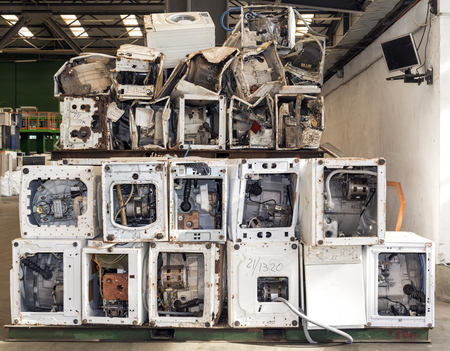 scrap trade: Used and dismantled washing machines waiting to be recycled on a recycling plant site. Sorted electronic garbage. Stock Photo