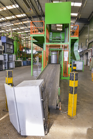 managing waste: Used refrigerator ready to be placed on an escalator and transported to be disassembled for recycling, inside a recycling plant