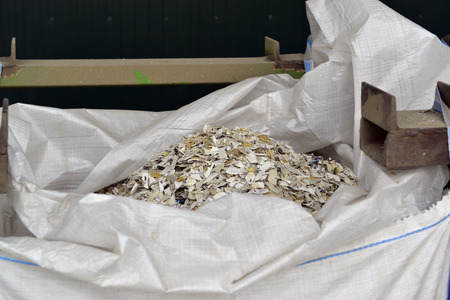managing waste: Close-up of recycled plastic waste cut in small pieces and separated in big bags, on a recycling plant