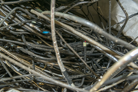 managing waste: Dismantled cables from various used electronic devices waiting to be recycled on a recycling plant site. Sorted electronic garbage.