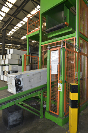 managing waste: Used refrigerator placed on an escalator and transported to be disassembled for recycling, inside a recycling plant Stock Photo