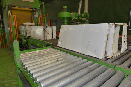 managing waste: Used refrigerators placed on an escalator and transported to be disassembled for recycling, inside a recycling plant
