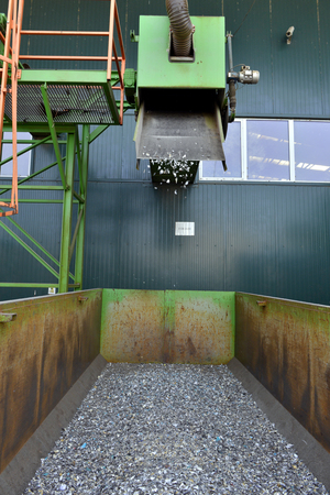 managing waste: Recycled plastic waste is cut in small pieces and separated in containers, on a recycling plant Stock Photo