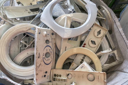 segregated: Various components from dismantled washing machines waiting to be recycled on a recycling plant site. Sorted electronic garbage.