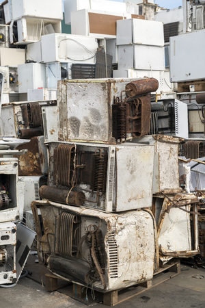 managing waste: Piles of used and thrown away washing machines waiting to be recycled on a recycling plant site
