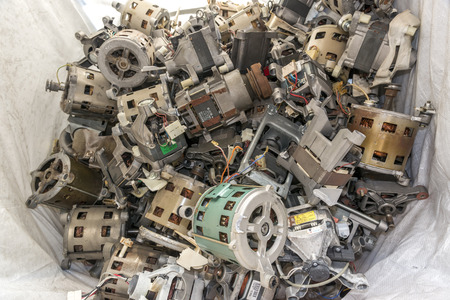 managing waste: Various components from dismantled washing machines waiting to be recycled on a recycling plant site. Sorted electronic garbage.
