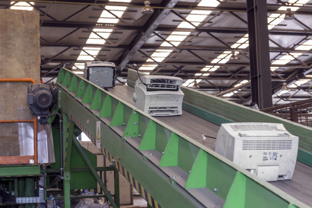 managing waste: Used office printing machines on an escalator, ready to be disassembled for recycling, inside a recycling plant