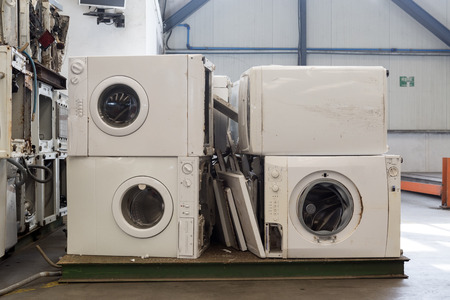 segregated: Piles of used and thrown away washing machines waiting to be recycled on a recycling plant site