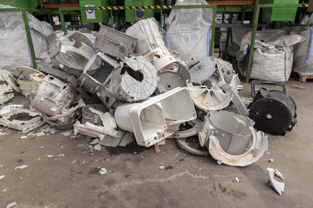 managing waste: Washing machines disassembled components waiting to be recycled inside a recycling plant site Stock Photo