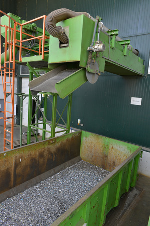 segregated: Recycled plastic waste is cut in small pieces and separated in containers, on a recycling plant Stock Photo