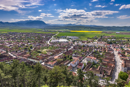 viewed: Spring view over Rasnov city, in Brasov county (Romania), with Piatra Craiului mountains in the background. Picturesque medieval town viewed from above, with mountains landscape
