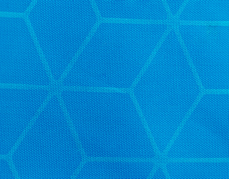 Macro detail view of woven synthetic waterproof blue nylon clothing fabric. Water Resistant Textile Coating Close Up. Stock Photo