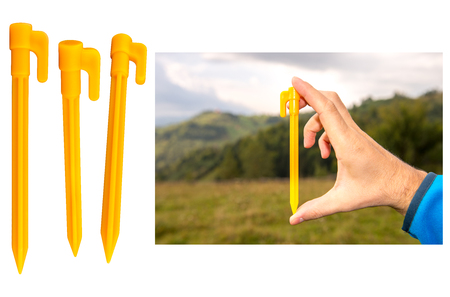 Yellow plastic tent stakes or pegs for camping. Three stakes in different positions and a demo image with natural background. Isolated on white background, clipping paths included.