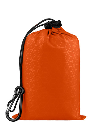 Very compact orange nylon pocket blanket in a drawstring bag with a carabiner. Thin tarp or footprint for outdoor activities. Isolated on white background, clipping path included. Stock Photo