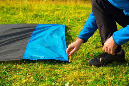 Young man pinning down a waterproof nylon blanket for resting on the grass, with yellow plastic tent stakes or pegs.