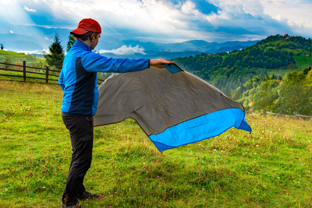 Young man unfolding down a waterproof nylon blanket for resting on the grass, on a beautiful mountain landscape. Hiker concept for summer designs. Stock Photo