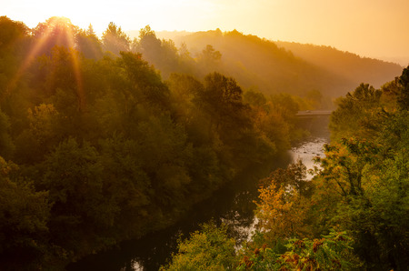Magical sunrise over deep foggy autumn forest along a river. First rays of sun through fog and trees on slopes. Scenic park fall landscape of misty old forest with sun rays, shadows and fog.