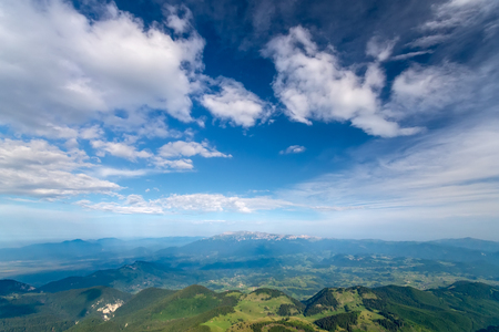 Breathtaking panoramic view of magnificent Rucar-Bran area between the Piatra Craiului and Bucegi mountains in the Romanian Carpathians. Natural alpine scenery landscape of mountains and dramatic cloudy sky.