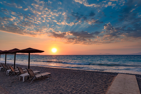 Beautiful sunset contre-jour on the sea shore, in a beach resort, with comfortable sunbeds and umbrellas