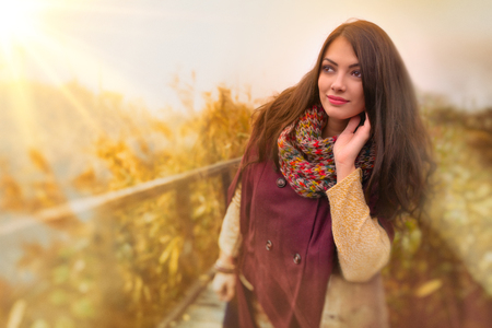 A gorgeous romantic young woman with beautiful long brown hair enjoying the autumn weather outdoors. Young woman head shot, retouched, double exposure, vibrant tinted colors, vintage look Foto de archivo