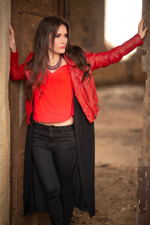 Fashion concept portrait of a gorgeous young woman in red leather jacket and black skirt outfit, sitting in a door of an old abandoned building and looking away. Body shot, retouched, vibrant colors Stok Fotoğraf