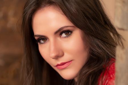 Retrato de moda de una hermosa mujer joven con chaqueta de cuero roja, sentada en una puerta de un antiguo edificio abandonado, mirando a la cámara. Disparo en la cabeza, retocado para una piel perfecta, colores vibrantes