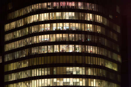 Multi-storey office building at night. Late night at office. Late night overtime in a modern office building 版權商用圖片